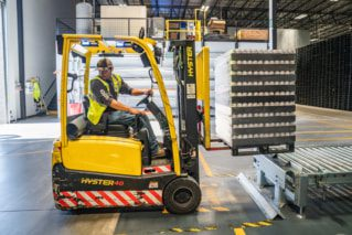 Warehouse worker moving product with a forklift